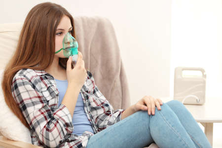 Young woman using nebulizer for asthma and respiratory diseases at home