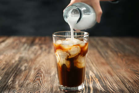 Pouring milk into glass of cold brew coffee on dark table 版權商用圖片