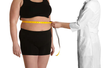 Doctor measuring stout adult woman on white background. Weight loss concept