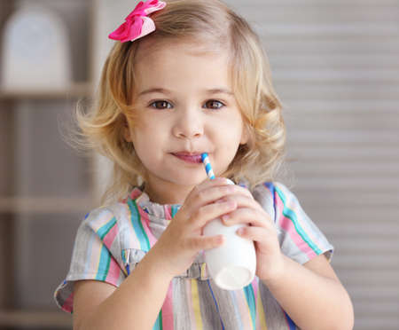 Cute little girl drinking yogurt at home