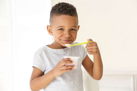 Cute African American boy eating yogurt at home
