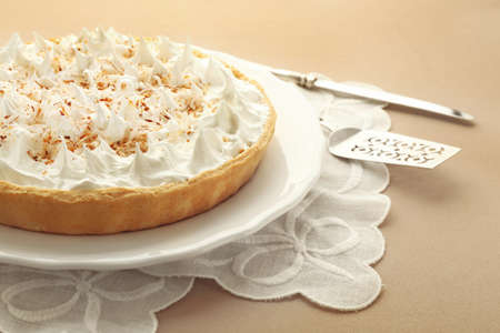 Vintage napkin and plate with delicious coconut cream pie on light background