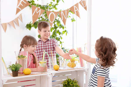 Cute little kids selling lemonade at counter