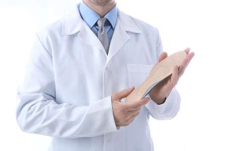 Orthopédiste masculin avec semelle intérieure sur fond blanc, gros plan% 00 Banque d'images