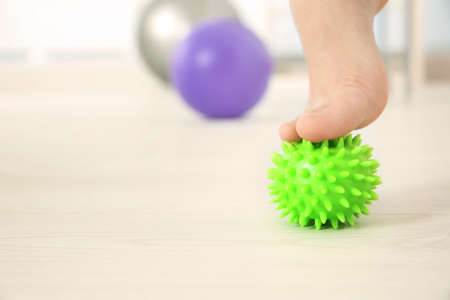 Foot of woman doing exercises with rubber ball in clinic Stock Photo