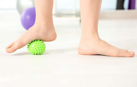 Feet of woman doing exercises with rubber ball in clinic Stock Photo