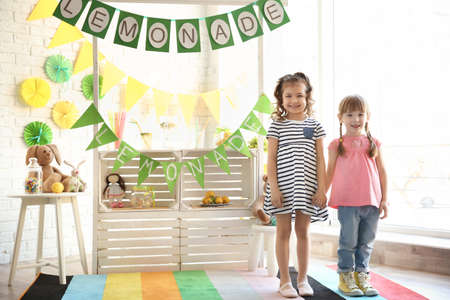 Cute little girls and stand with lemonade on background