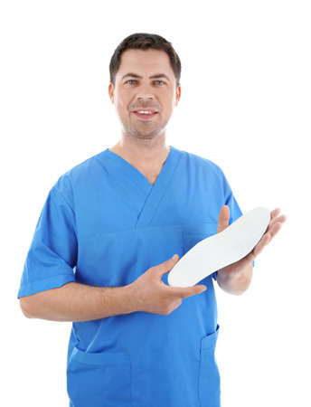 Male orthopedist with insole on white background