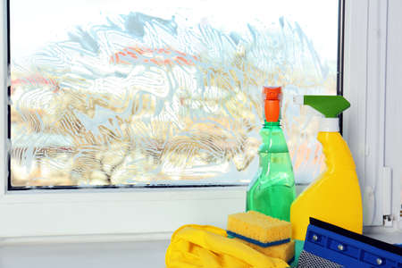 Cleaning supplies on window sill Stock Photo