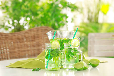 Glassware with refreshing lemonade on table outdoor