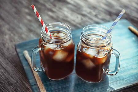 Mason jars with cold brew coffee on wooden tray