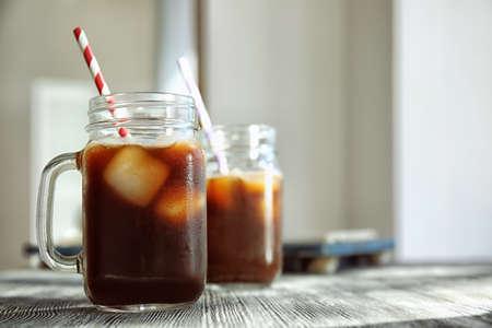 Weckglas mit kaltem Gebräukaffee und -stroh auf Holztisch