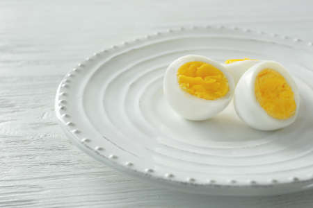 White ceramic plate with sliced hard boiled eggs on wooden table. Nutrition concept