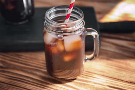 Mason jar with cold brew coffee and straw on wooden table