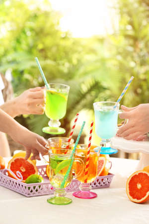 Friends cheering with glasses of  different kinds of lemonade on picnic
