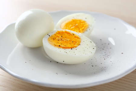 White ceramic plate with hard boiled eggs on light table. Nutrition concept