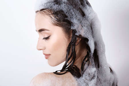 Young woman taking shower on white background
