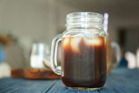 Mason jar with cold brew coffee and ice on wooden table
