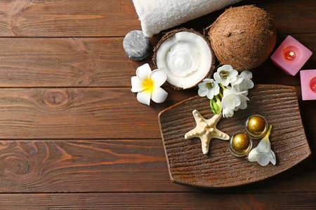 Beautiful spa composition with coconut body care products on wooden background