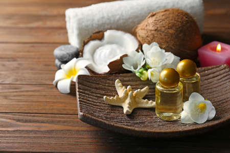 Platter with coconut oil in bottles, starfish and flowers on wooden table