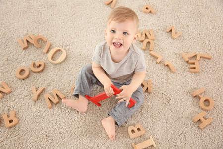 Nettes kleines Kind mit den hölzernen Buchstaben , die auf Teppich zu Hause sitzen Standard-Bild
