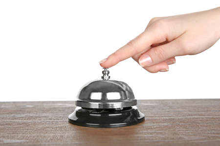 Main féminine sonne une cloche de service sur une table en bois sur fond blanc Banque d'images - 97724581