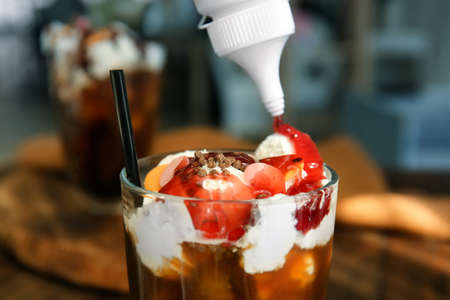 Pouring topping onto dessert with cold brew coffee in glass on table, closeup Stock Photo