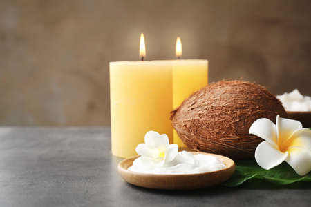 Wooden bowl with cream, coconut and candles on grey table