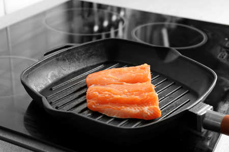 Grill frying pan with slice of salmon on induction stove