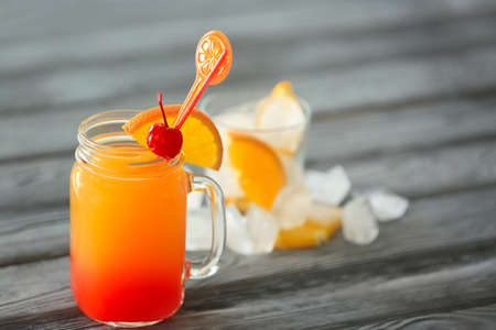 Mason jar of delicious tequila sunrise cocktail on table Stock Photo