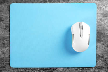 Blank mat and wireless mouse on textured background Imagens - 98132493