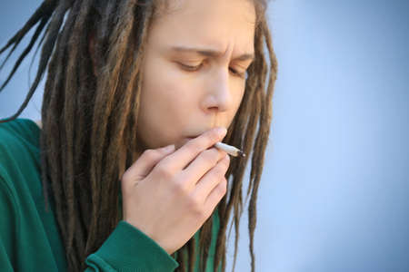 Young boy smoking weed on light background Stock Photo