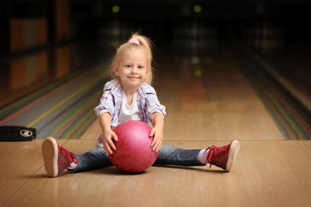 Cute child with ball in bowling club