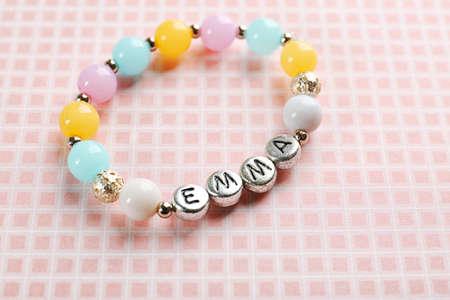 Bracelet with baby name EMMA on color cloth Banco de Imagens