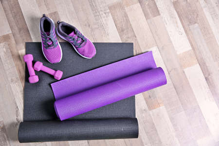 Yoga mats, sneakers and dumbbells on wooden floor