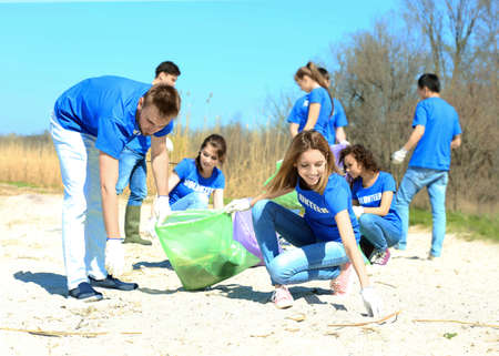Young volunteers gathering garbage outdoors Banco de Imagens