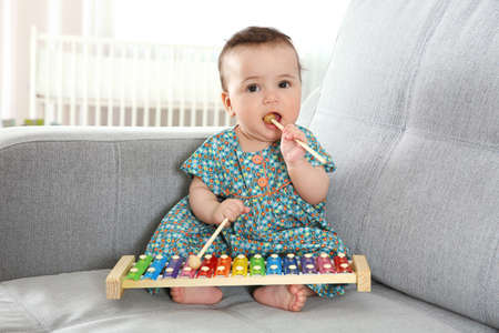 Cute little baby with xylophone at home