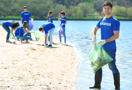 Handsome young volunteer with team gathering garbage on river bank