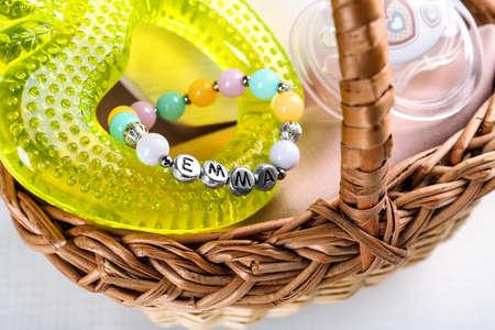 Bracelet with baby name Emma in basket on white background Stock Photo