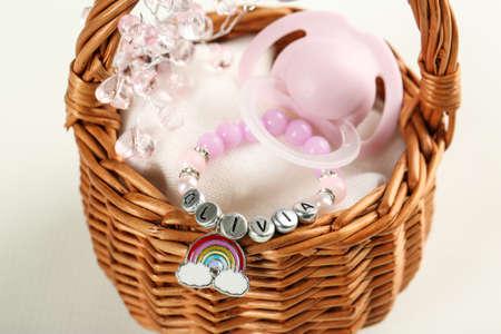 Bracelet with baby name Olivia in basket on white background