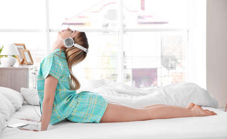 Woman doing yoga and listening to the music on bed at home Stock Photo