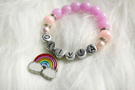 Bracelet with baby name Olivia on white fluffy background