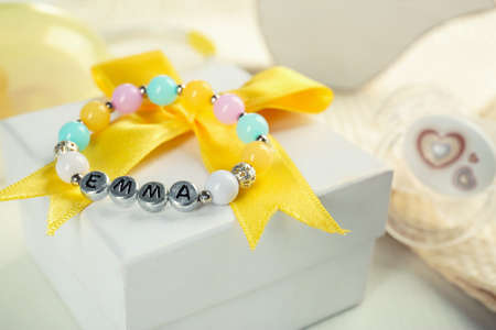 Bracelet with baby name Emma on white gift box