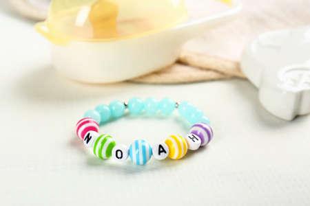 Bracelet with baby name Noah on white fabric background