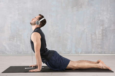 Man doing yoga and listening to the music at home