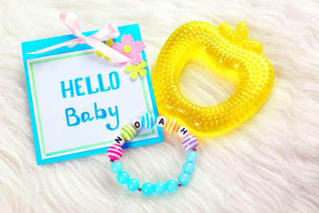 Composition with baby name bracelet on white fluffy background Stock Photo