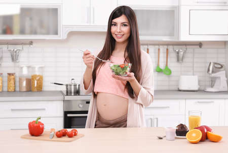 Young pregnant woman having breakfast in kitchen