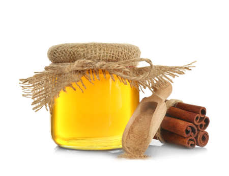 Jar with honey, wooden scoop and cinnamon on white background