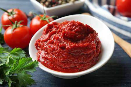 Keramische kom met tomatensaus en ingrediënten op houten tafel Stockfoto - 97870921