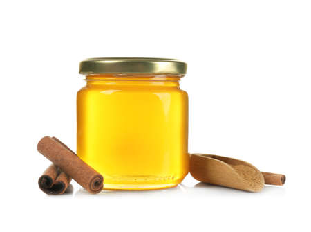 Jar with honey, cinnamon and wooden scoop on white background Stock Photo